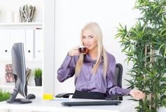 Piękna blounde młoda kobieta pije gorącej herbaty przy biurem Zdjęcia Royalty Free