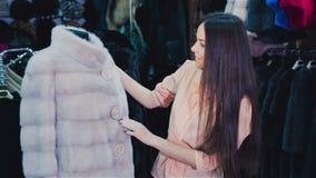 Piękna brązowowłosa dziewczyna wybiera futerkowego żakiet w sklepie na zakupy serifs zbiory