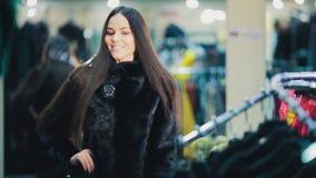 Piękna brązowowłosa dziewczyna wybiera futerkowego żakiet w sklepie na zakupy serifs zbiory wideo