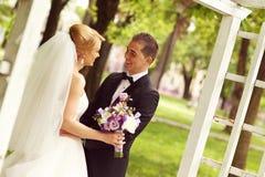 Piękna bridal para ma zabawę w parku na ich dnia ślubu kwiatu bukiecie Zdjęcie Royalty Free