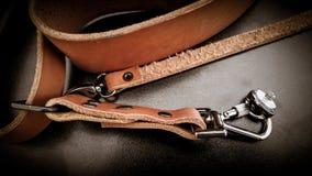 Piękna brown ręcznie robiony rzemienna kamera temblaka patka na czarnym tle zdjęcie stock
