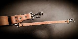 Piękna brown ręcznie robiony rzemienna kamera temblaka patka na czarnym tle obraz royalty free