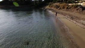 Piękna brunetka biega wzdłuż plaży blisko oceanu zdjęcie wideo