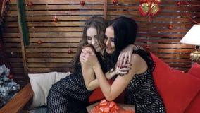 Piękna brunetka i jasnogłowe dziewczyny w czarnym wieczór sukni uściśnięciu po wymiany nowego roku ` s prezenty Fotografia Stock