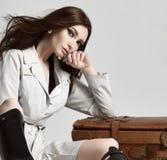 Piękna brunetka modnisia kobieta w szarej jesieni kurtce z wietrzną włosianą siedzącą pobliską rzemienną brown retro podróży torb obraz stock