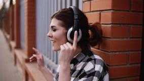 Piękna brunetka opiera na ceglanym ogrodzeniu outdoors, słuchający muzyka na hełmofonach z oczami zamykającymi Czuje muzykę zbiory