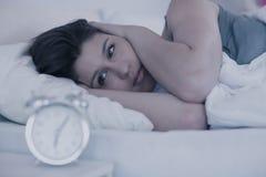 Piękna brunetka patrzeje budzika w jej łóżku Zdjęcie Stock