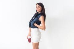 Piękna brunetka pozuje w przypadkowy eleganckim odziewa na białym tle, trzyma czerwoną filiżankę oddalona kawa, patrzeje obraz royalty free