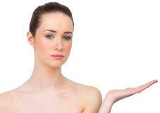 Piękna brunetka przedstawia z ręką Fotografia Royalty Free