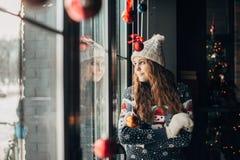 Piękna brunetka w Bożenarodzeniowym pulowerze przyglądającym out okno Obrazy Stock