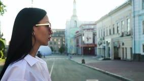 Piękna brunetka w eleganckich okularach przeciwsłonecznych chodzi wzdłuż miastowej ulicy w zwolnionym tempie zbiory
