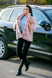 Piękna brunetka w lekkim futerkowym żakiecie i czarni spodniowi spacery zestrzelamy ulicę obok samochodu na jesień słonecznym dni fotografia royalty free