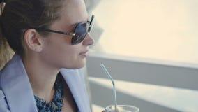 Piękna brunetka w okularach przeciwsłonecznych siedzi przy lato tarasem i relaksuje z kawą zbiory