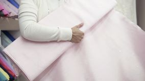 Piękna brunetka wybiera tkaninę w tkankowym sklepie Bierze rolkę światło i stosuje ciało - różowa tkanina zbiory