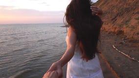 Piękna brunetka z długie włosy bieg na plaży przy zmierzchu tłem zbiory wideo