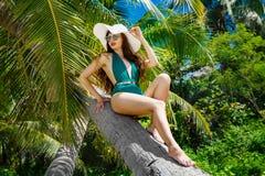 Piękna brunetka z długie włosy w zielonym kostiumu kąpielowym i stra Fotografia Royalty Free