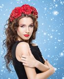 Piękna brunetka z jaskrawą czerwoną kwiat kapitałką nad błękitną wygraną obrazy stock