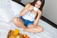 Piękna brunetki dziewczyna je zdrowego śniadanie i pije kawę w łóżku obraz stock