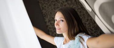 Piękna brunetki dziewczyna pcha zasłony na ranku okno obrazy royalty free