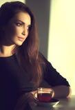 Piękna brunetki dziewczyna pije herbaty lub kawy Obraz Stock