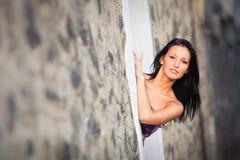 Piękna brunetki dziewczyna pozuje blisko skały ściany Fotografia Royalty Free