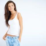 Piękna brunetki dziewczyna pozuje nad bielem fotografia royalty free