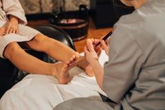 Piękna brunetki dziewczyna robi nożnemu masażowi leczniczy Zdjęcie Royalty Free