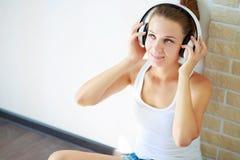 Piękna brunetki dziewczyna słucha muzyka z hełmofonami podczas gdy siedzący na podłoga w pustym pokoju na białej ścianie obraz royalty free