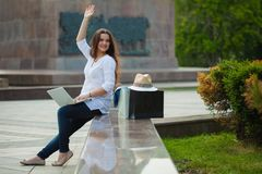 Piękna brunetki dziewczyna siedzi na ulicie z robić zakupy i laptopem Macha jej rękę zdjęcie stock