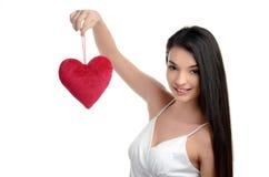 Piękna brunetki dziewczyna trzyma up czerwonego serce. Szczęśliwa kobieta, walentynki. Zdjęcie Stock