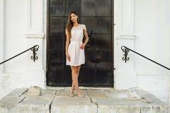 Piękna brunetki dziewczyna w czarnym metalu drzwi na schodek pozach czarnooki twarzy seksowna kobieta stylowa mody Garbnikująca k Fotografia Stock