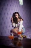 Piękna brunetki dziewczyna w drelichu zwiera i biała bluzka pozuje na bez textured tle z dwa napojów szkłami pierwszoplanowymi Fotografia Royalty Free
