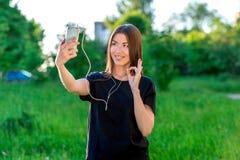 Piękna brunetki dziewczyna w lecie w parku outdoors Chwyty w twój ręce smartphone opowiadają ogólnospołeczne sieci fotografia stock