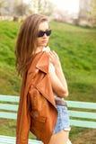 Piękna brunetki dziewczyna w okularach przeciwsłonecznych z kurtki stojakami w parku zdjęcia stock