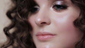 Piękna brunetki dziewczyna z doskonale kędzierzawym włosy i klasyczny makijaż pozuje w studiu, Piękno Twarz zbiory wideo