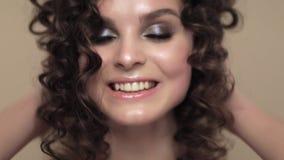 Piękna brunetki dziewczyna z doskonale kędzierzawym włosy i klasyczny makijaż pozuje w studiu, Piękno Twarz zdjęcie wideo