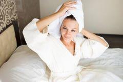 Piękna brunetki dziewczyna z ręcznikiem na jej głowie w łóżku Brał prysznic Ranku pojęcie obrazy stock