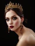 Piękna brunetki dziewczyna z złotą koroną, kolczykami i profes, zdjęcie stock