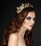 Piękna brunetki dziewczyna z złotą koroną, kolczykami i profes, obraz royalty free