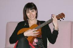 Piękna brunetki kobieta bawić się ukulele Zdjęcie Royalty Free