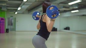 Piękna brunetki kobieta kuca z barbell w gym koncepcja kulowego fitness pilates złagodzenie fizycznej zdjęcie wideo