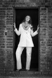 Piękna brunetki kobieta w białym zima żakiecie, cajgach pozuje w stajni drzwi i, Obraz Stock