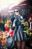 Piękna brunetki kobieta wybiera kwiaty przy kwiaciarnia sklepem z rękawiczkami. Modna kobieta z okularami przeciwsłonecznymi i kie Zdjęcie Stock