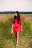 piękna brunetki kobieta z butami w ręce na polu Zdjęcie Royalty Free