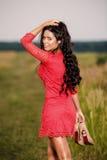 piękna brunetki kobieta z butami w ręce na polu Fotografia Royalty Free