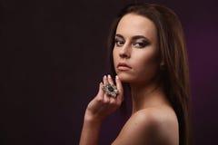 Piękna brunetki kobieta z fachowym makeup i fryzura pokazuje w studiu dużych kolczyki i pierścionek Zdjęcia Royalty Free