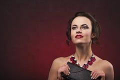 Piękna brunetki kobieta z fachowym makeup i fryzura z dużej kolii przyglądającym up mieniem czernimy torebkę Zdjęcie Royalty Free