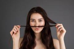 Piękna brunetki kobieta z niebieskimi oczami bawić się z jej włosy fotografia stock