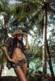Piękna brunetki kobieta z słomianym kapeluszem i okularami przeciwsłonecznymi w tropikalnym lesie obrazy stock