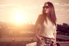 Piękna brunetki młoda kobieta pozuje nad zmierzchu miasta tło obraz stock
